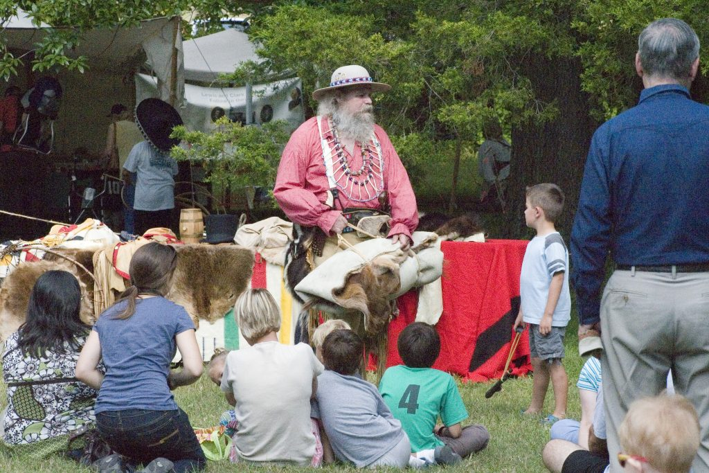 Heritage Festival, children gathered around a craftsman for stories
