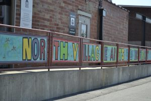 painted sign that says 'North Village Arts District' in all colors