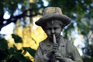 statue of a boy with a hat playing a musical instrument