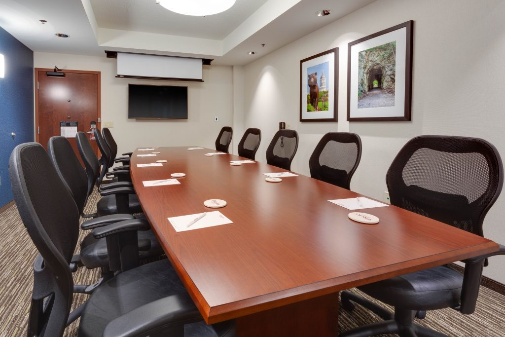 Drury Plaza Hotel meeting room with wooden table and 10 black chairs